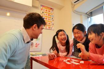 外国人講師から3人の女の子が英語のグループレッスンを受けている