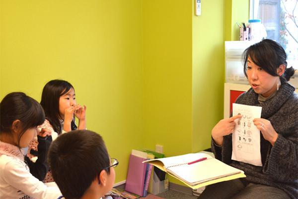 女性英語講師から英会話のレッスンを受ける3人の子供
